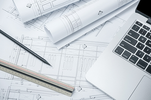 black-pencil-and-computer-laptop-on-architectural-drawing-paper-for-construction