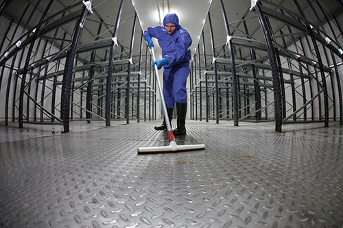 worker  cleaning floor in empty storehouse